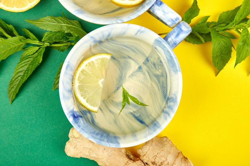 Healthy tea two cups with lemon, ginger, mint. On a color background. Warm drink for cold flu winter fall days. Flat lay. Copy space. Top view royalty free stock image