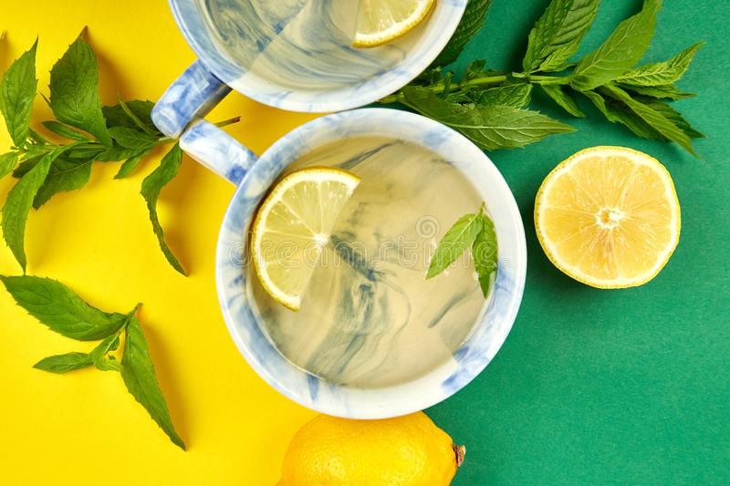 Healthy tea two cups with lemon, ginger, mint. On a color background. Warm drink for cold flu winter fall days. Flat lay. Copy space. Top view stock image