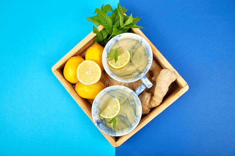 Healthy tea two cups with lemon, ginger, mint. In wooden tray on a color background. Warm drink for cold flu winter fall days. Flat lay. Copy space. Top view stock image