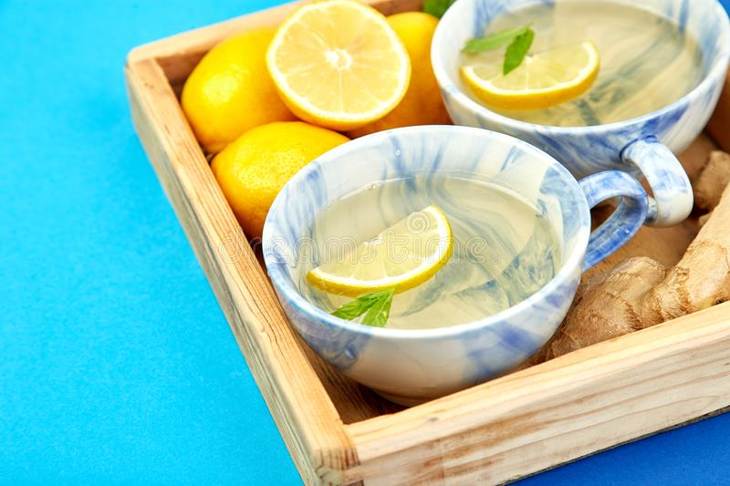 Healthy tea two cups with lemon, ginger, mint. In wooden tray on a color background. Warm drink for cold flu winter fall days. Flat lay. Copy space. Top view stock photography