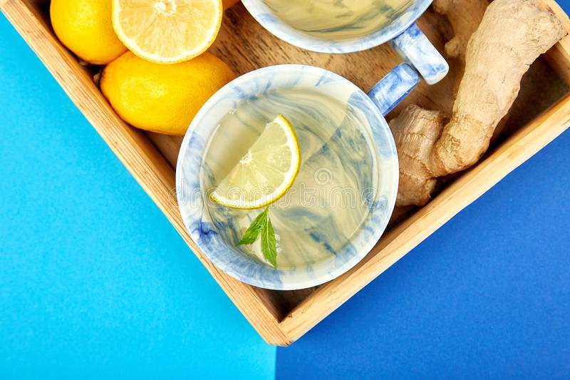 Healthy tea two cups with lemon, ginger, mint. In wooden tray on a color background. Warm drink for cold flu winter fall days. Flat lay. Copy space. Top view royalty free stock photos