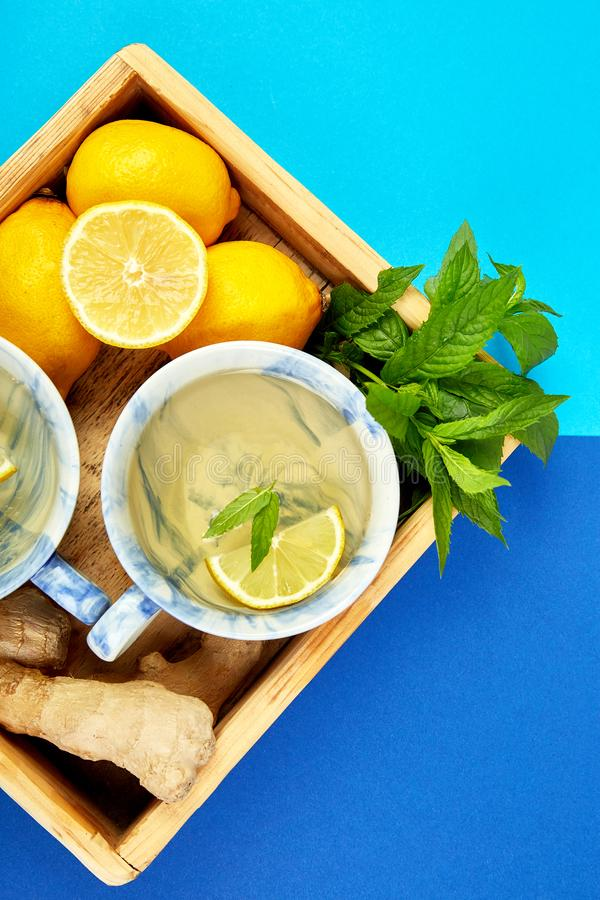 Healthy tea two cups with lemon, ginger, mint. In wooden tray on a color background. Warm drink for cold flu winter fall days. Flat lay. Copy space. Top view stock photos