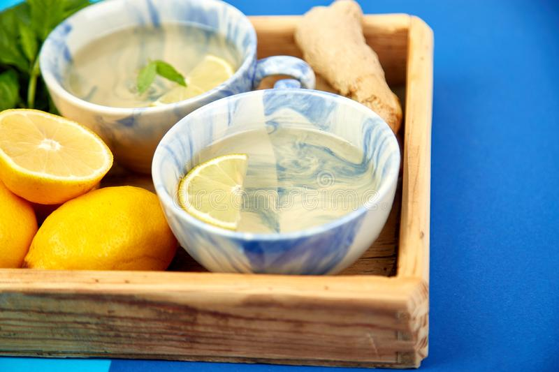Healthy tea two cups with lemon, ginger, mint. In wooden tray on a color background. Warm drink for cold flu winter fall days. Flat lay. Copy space. Top view royalty free stock image