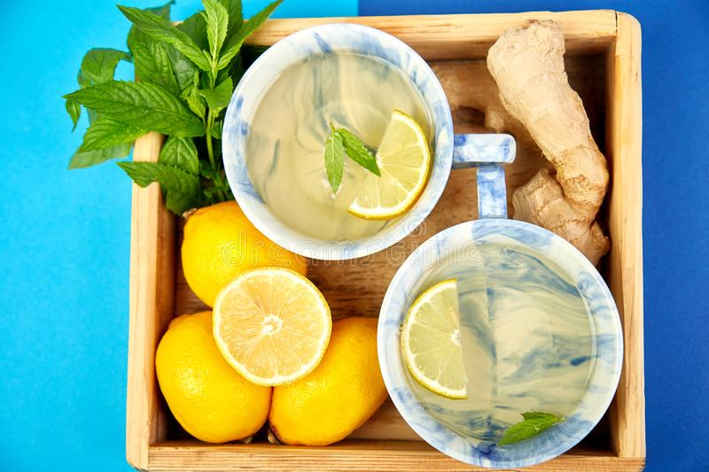 Healthy tea two cups with lemon, ginger, mint. In wooden tray on a color background. Warm drink for cold flu winter fall days. Flat lay. Copy space. Top view royalty free stock photography