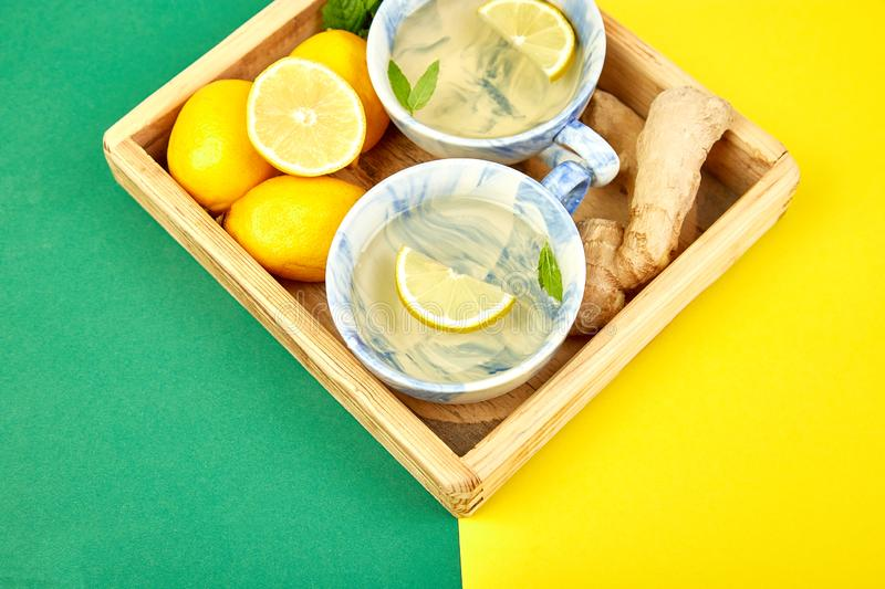 Healthy tea two cups with lemon, ginger, mint. In wooden tray on a color background. Warm drink for cold flu winter fall days. Flat lay. Copy space. Top view stock photo