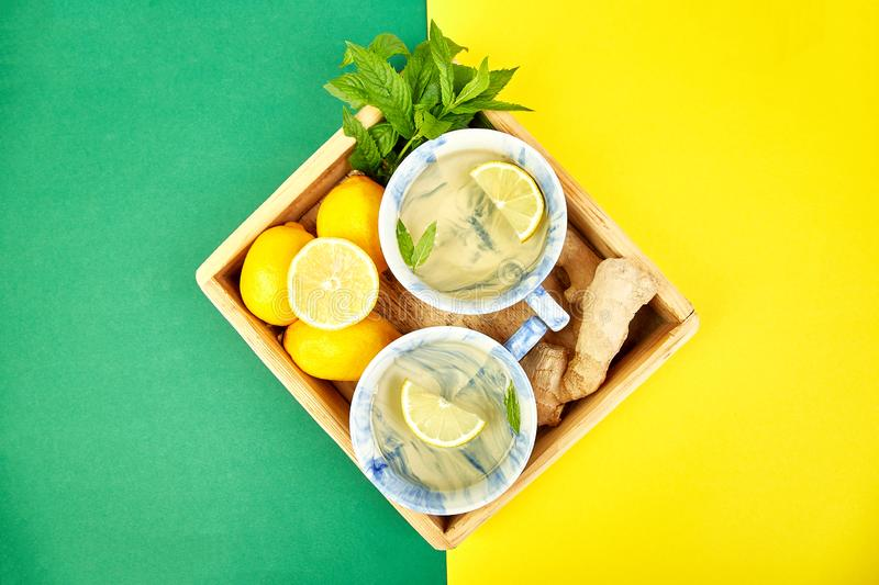 Healthy tea two cups with lemon, ginger, mint. In wooden tray on a color background. Warm drink for cold flu winter fall days. Flat lay. Copy space. Top view royalty free stock photo