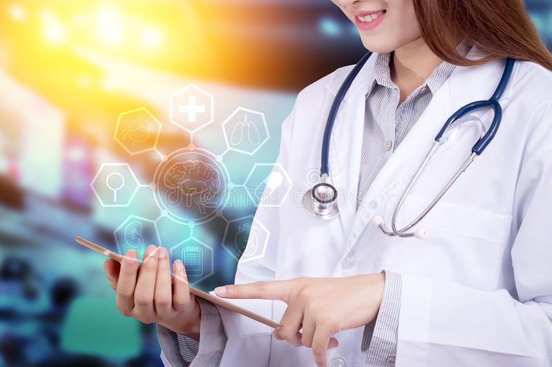 Healthy technology concept : Young Asian doctor using tablet royalty free stock photo