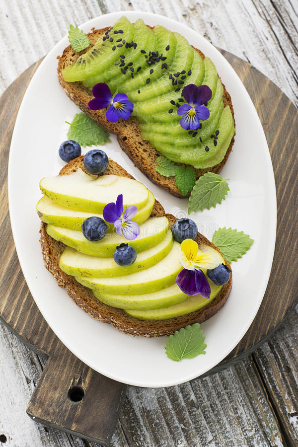 Healthy toast with green apple and juicy Kiwi with edible flowers of garden violas on a marble background. Color year royalty free stock photos