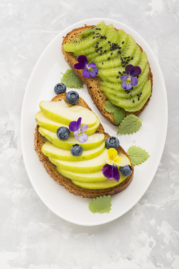 Healthy toast with green apple and juicy Kiwi with edible flowers of garden violas on a marble background. Color year. Greenery. Top royalty free stock photo