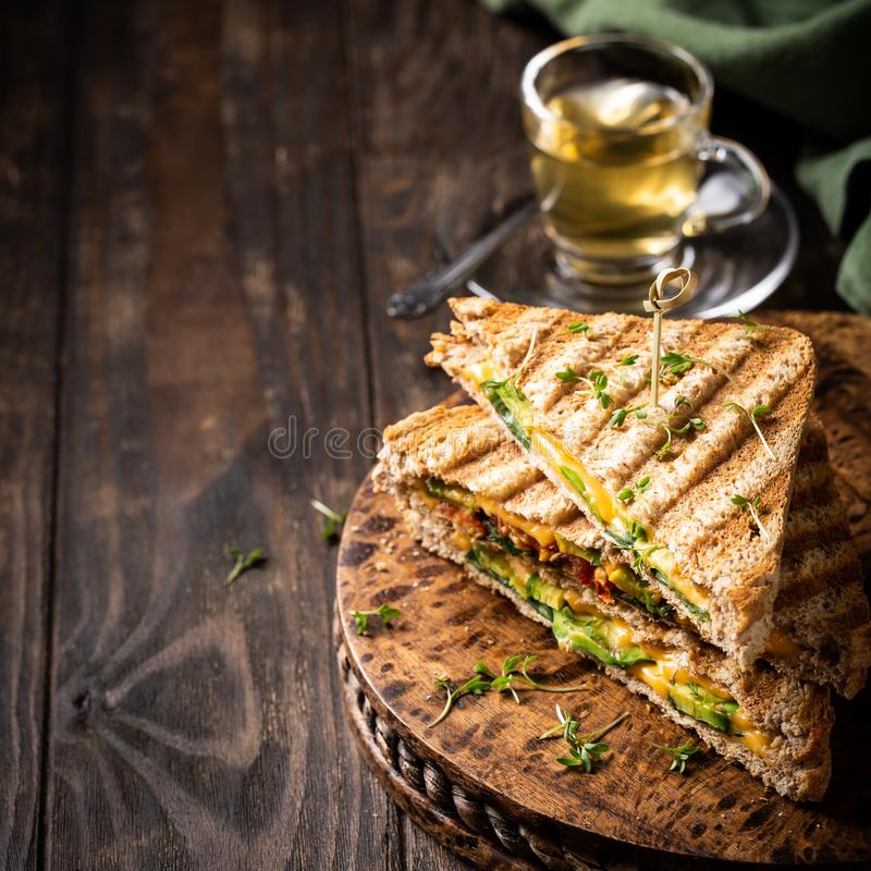 Healthy avocado toasts for lunch. Healthy toasts with avocado, cheddar cheese and tomatoes for breakfast or lunch. Vegetarian sandwiches. Plant-based diet. Whole stock photos