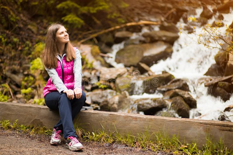Beautiful young woman happy near forest waterfall stock photography