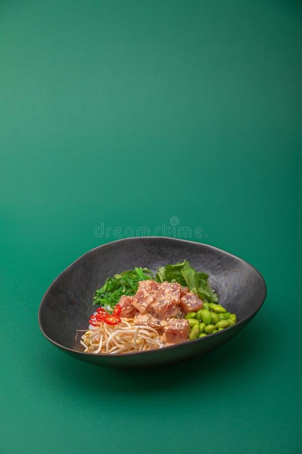 Healthy tuna poke bowl. Poke is a traditional Hawaiian dish influenced by japanese and asian cuisine. rice tuna seaweed royalty free stock photography