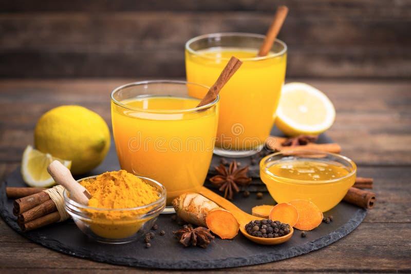 Healthy turmeric drink with honey, cinnamon, lemon and ginger stock photos