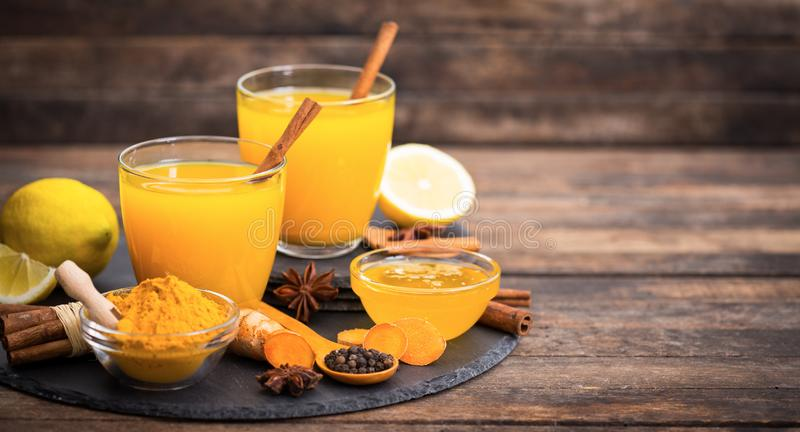 Healthy turmeric drink with honey, cinnamon, lemon and ginger royalty free stock photography