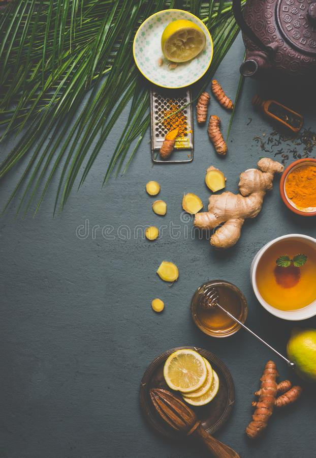 Healthy turmeric spice tea on gray background with teapot, cup of tea and ingredients: lemon, ginger, cinnamon sticks and honey. Top view. Immune boosting royalty free stock photography