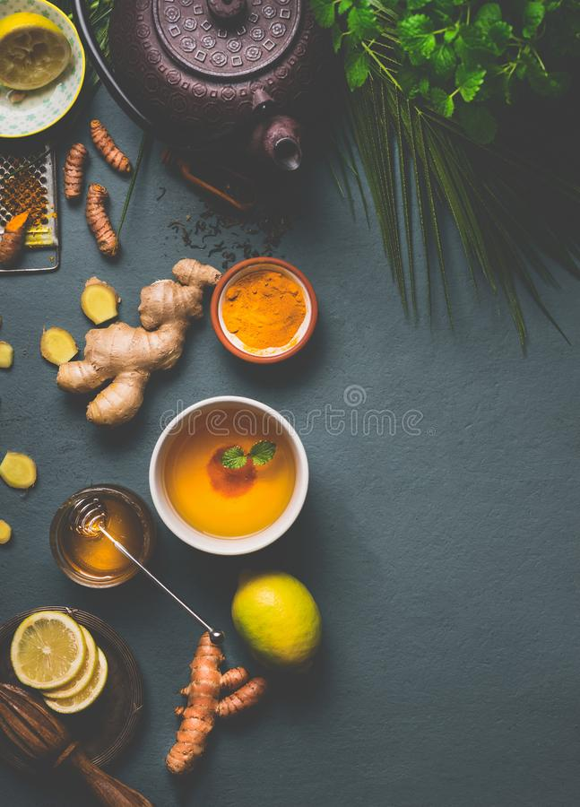 Healthy turmeric spice tea preparation on gray background with teapot, cup of tea, lemon, ginger, cinnamon sticks and honey. Top view. Immune boosting remedy stock photography