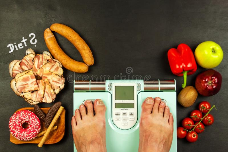 Healthy and unhealthy food. Obesity concept. Modern digital weight and bacon. Weight control on diet.  stock image