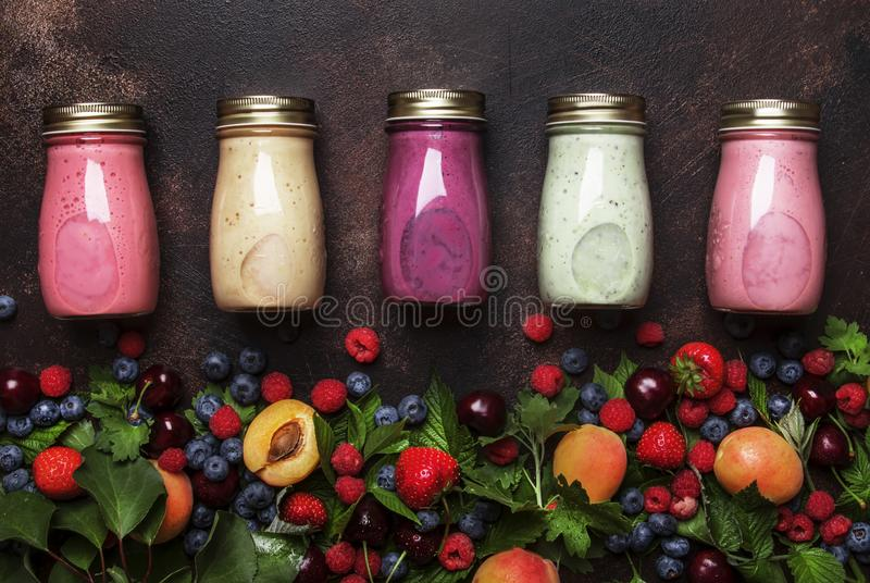 Healthy and useful colorful berry cokctalis, smoothies and milkshakes with yogurt, fresh fruit and berries on brown kitchen table. Colorful berry cokctalis stock photography