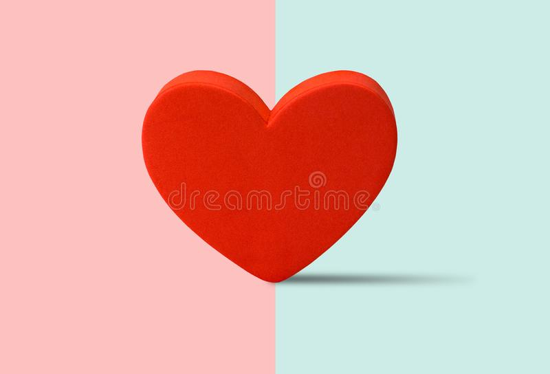 Red heart shape standing on half pink and blue color background. stock illustration