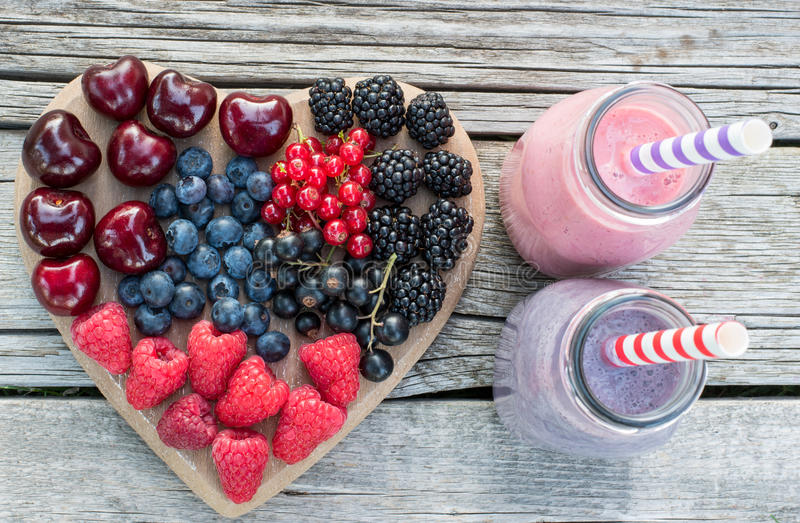 Healthy various fruits on heart and smoothies. Diet abstract concept . stock photography