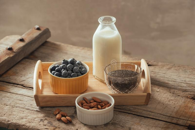 Healthy vegan breakfast. Bottled milk with chia, almond, fresh fruit and berries over wooden table background, copy space. Clean. Eating, weight loss royalty free stock photos