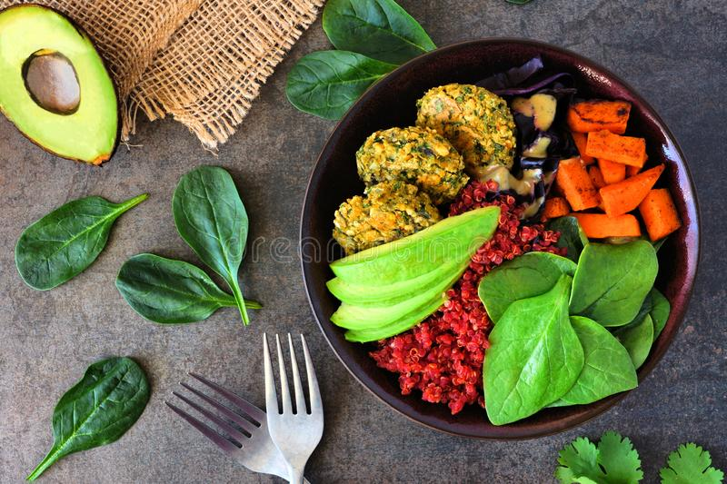Healthy vegan buddha bowl with falafels, beet quinoa, avocado, and vegetables on dark stone royalty free stock photo