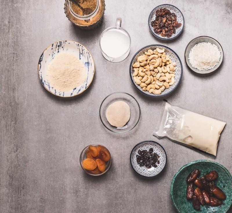 Healthy vegan diet ingredients bowls : cashew , almond flour, Coconut cream, non dairy milk, agar agar, Coconut butter, dried. Fruits on concrete background stock image