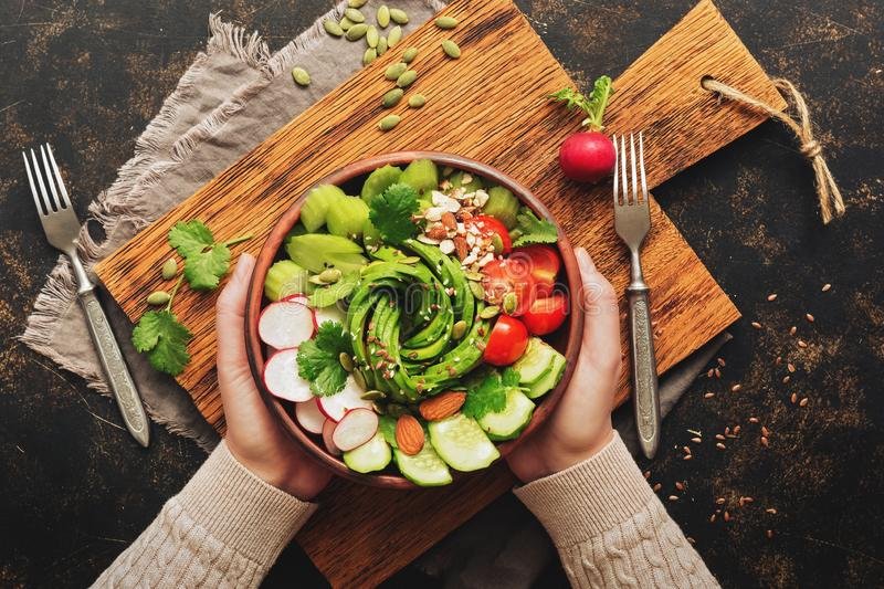 Healthy vegan diet salad with fresh vegetables-avocado, radish, tomato, cucumber, celery, nuts and seeds.Girl in wool sweater royalty free stock image
