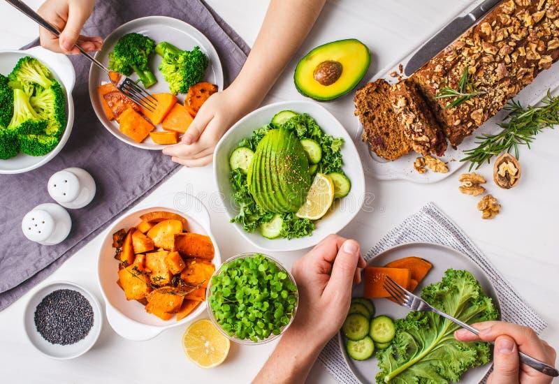 Healthy vegan food lunch, top view. Vegetarian dinner table, people eat healthy food. Salad, sweet potato, vegan cake, vegetables royalty free stock image