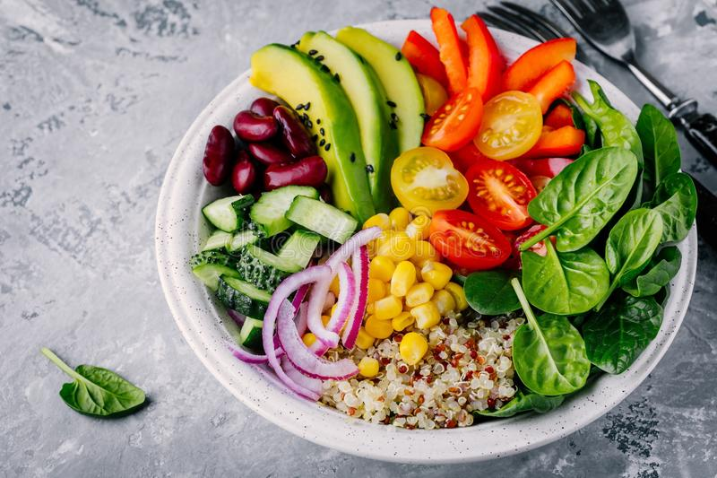 Healthy vegan lunch Buddha bowl. Avocado, quinoa, tomato, cucumber, red beans, spinach, red onion and red paprika vegetables salad. Top view stock photos