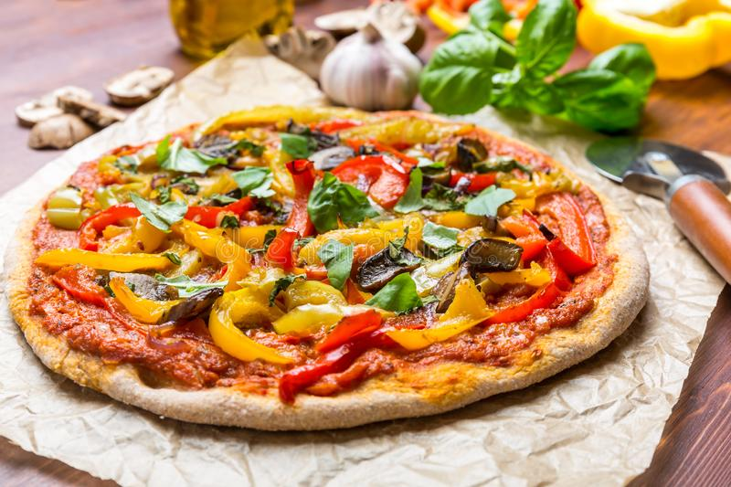 Tasty and Healthy Vegan Pizza and Ingridients. Delicious and Colourful Super Healthy Vegan Whole Grain Vegetables and Mushrooms Pizza on a Baking Paper with stock photography