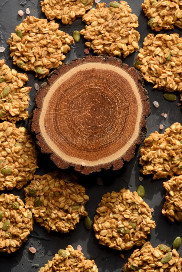 Healthy vegan snack concept. Oatmeal breakfast cookies and round wood slab on black background top view stock images