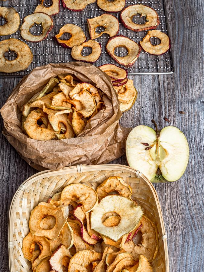 Tasty apple chips on wooden table, healthy vegan vegetarian fruit snack or ingredient for cooking. Healthy vegan vegetarian fruit snack or ingredient for cooking royalty free stock photos