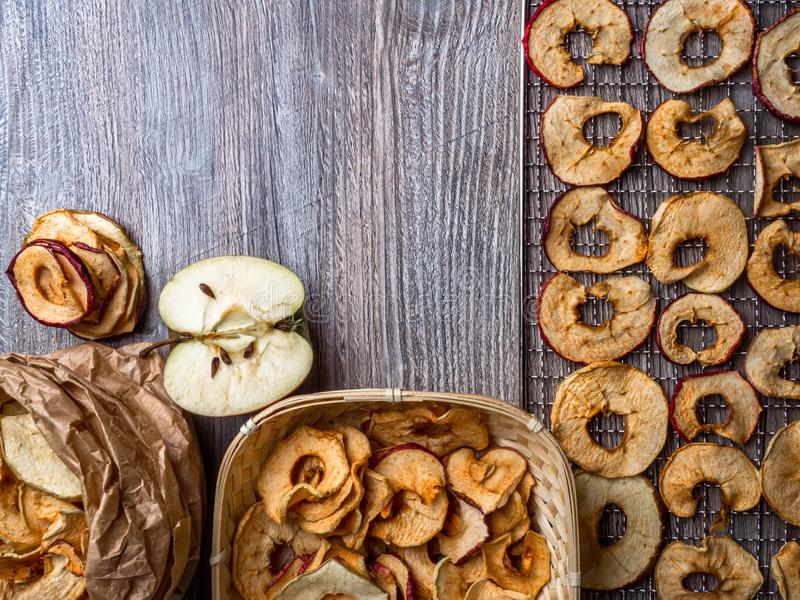 Tasty apple chips on wooden table, healthy vegan vegetarian fruit snack or ingredient for cooking. Healthy vegan vegetarian fruit snack or ingredient for cooking royalty free stock photo