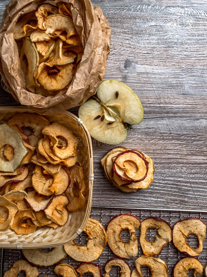 Tasty apple chips on wooden table, healthy vegan vegetarian fruit snack or ingredient for cooking. Healthy vegan vegetarian fruit snack or ingredient for cooking stock photography