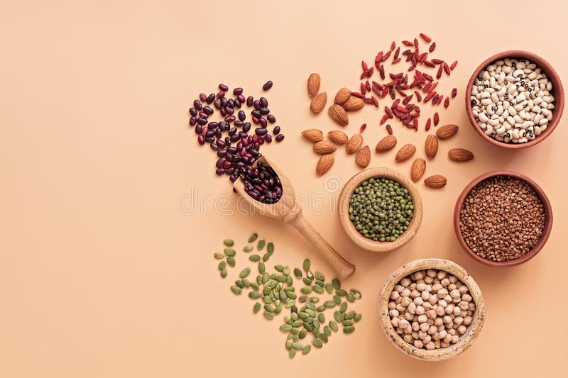 Healthy vegan and vegetarian super foods, beans, pumpkin seeds, chickpeas, buckwheat, mung beans, almonds and goji berries on a royalty free stock images