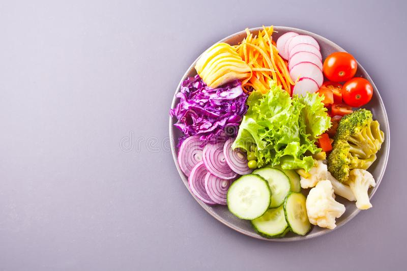 Healthy vegetable buddha bowl lunch with quinoa, red cabbage, tomatoes, onion, green salad, cucumber on gray background. Top view stock photo