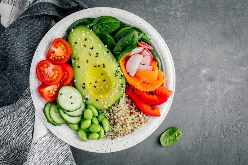 Healthy vegetable lunch Buddha bowl. Avocado, quinoa, tomatoes, cucumbers, radishes, spinach, carrots, paprika and edamame beans s stock images