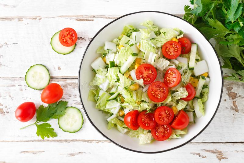 Healthy vegetable salad of chinese cabbage, corn, cucumbers and tomatoes. Delicious vegetarian dietary lunch. Vegan food. Top view royalty free stock photos