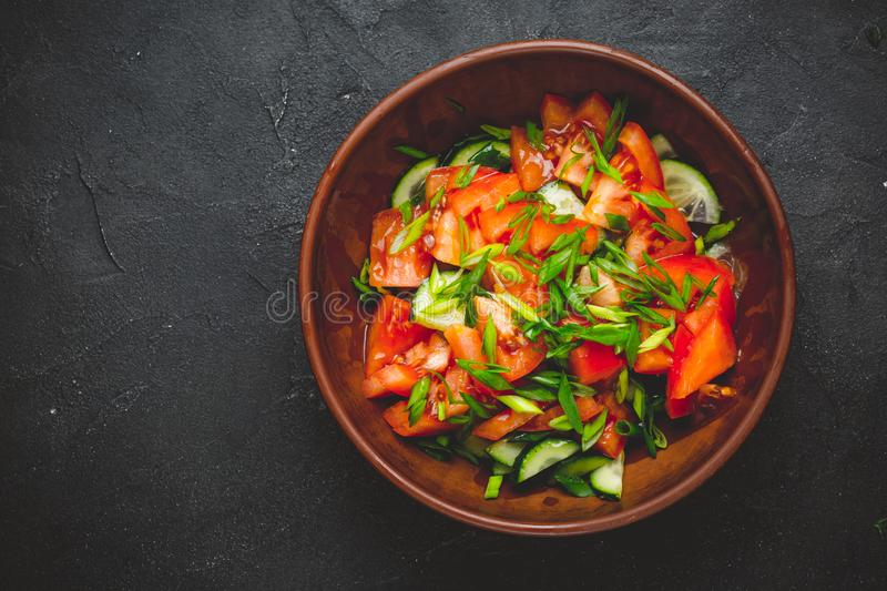 Healthy vegetable salad of fresh tomato, cucumber, onion, spinach, lettuce royalty free stock photography