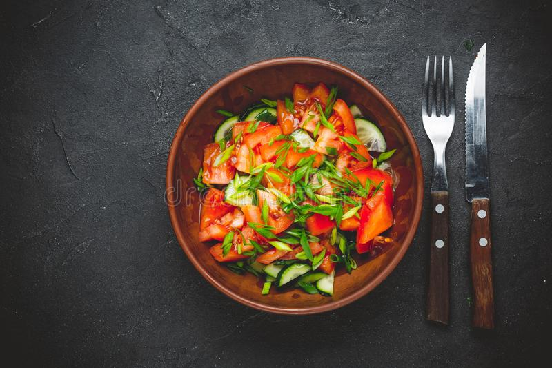 Healthy vegetable salad of fresh tomato, cucumber, onion, spinach, lettuce royalty free stock image