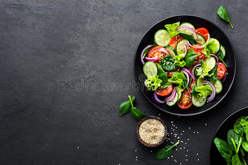 Healthy vegetable salad of fresh tomato, cucumber, onion, spinach, lettuce and sesame on plate. Diet menu royalty free stock photo