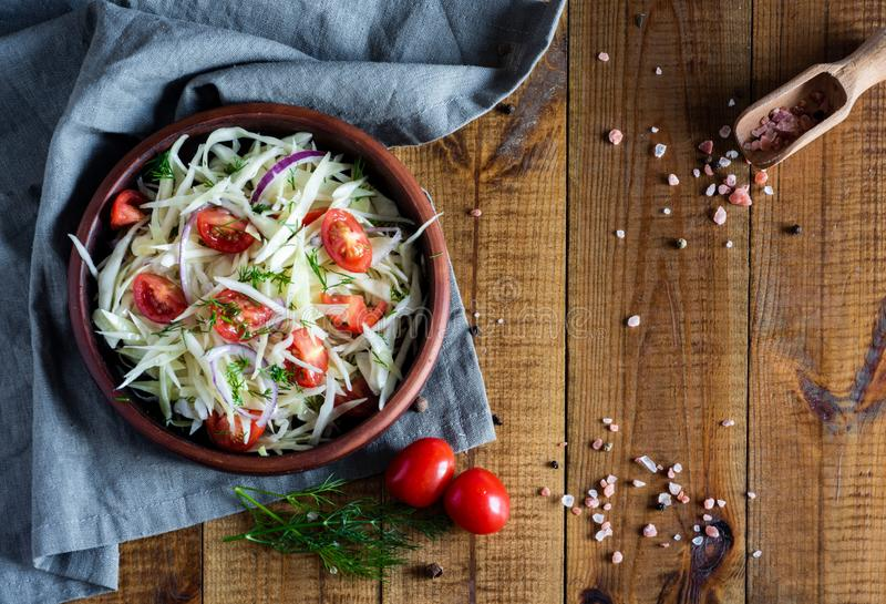 Healthy vegetable salad with tomatoes, fresh cabbage, herbs and olive oil in a clay bowl on a wooden table. Vegetarian dish royalty free stock photography