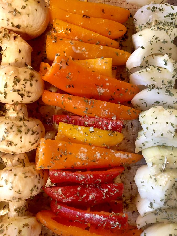 Healthy vegetable skewers ready to grill, nutritious red orange and yellow peppers with mushrooms and onions stock photo