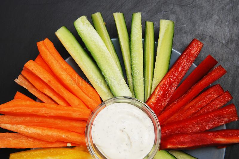 Healthy Vegetable Vegan Vegetarian Vitamine Sticks on Round Plate Yogurt Sauce Black Background royalty free stock photo