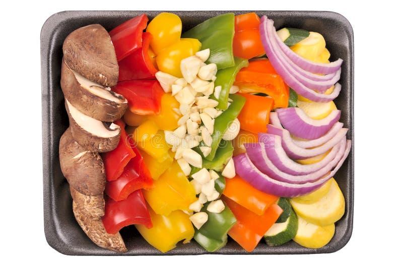 Healthy Vegetable Stir Fry. Convenient store prepared stir fry vegetables on a styrofoam tray. Isolated. (Portobello mushrooms, peppers, garlic, onion, squash stock image
