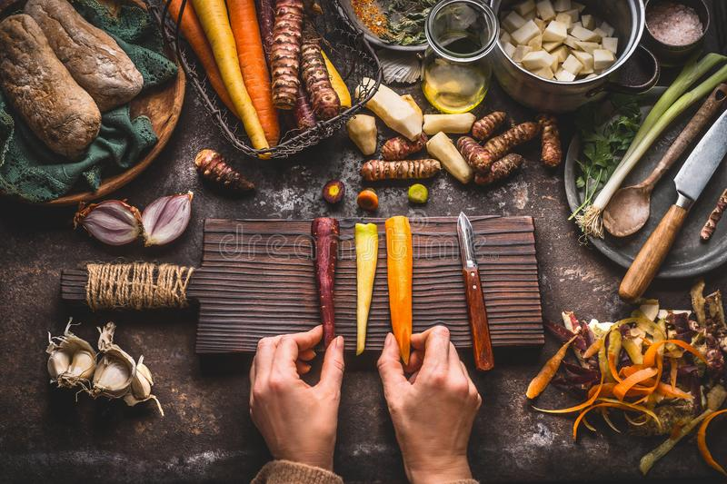 Healthy vegetables cooking and eating concept. Female woman hands holding colorful carrots on kitchen table background with vegeta stock image