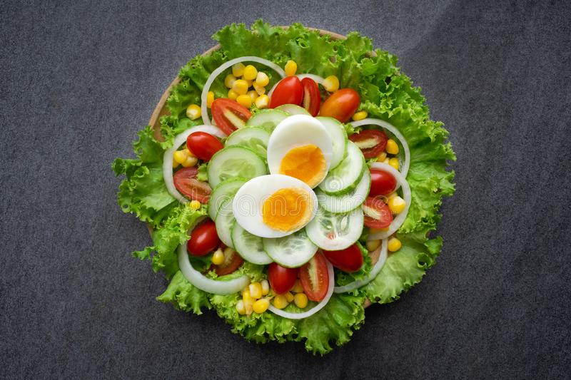 Healthy vegetables salad with boiled egg in wooden dish on table for vegetarian stock photos