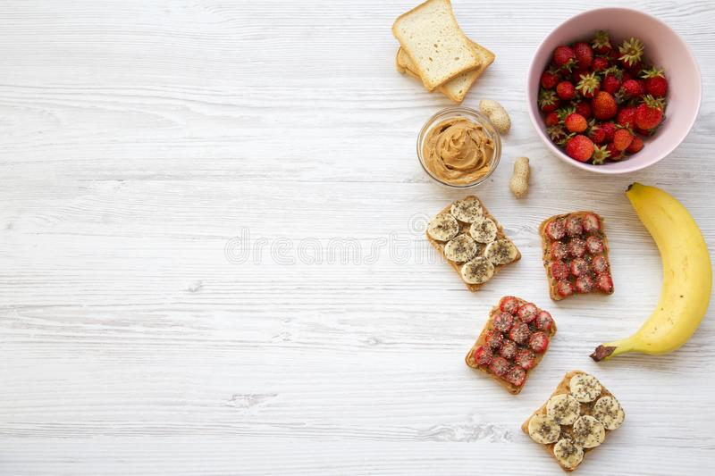 Healthy vegetarian breakfast with ingredients, diet concept. Vegan toasts with fruits, seeds, peanut butter over white wooden back royalty free stock images