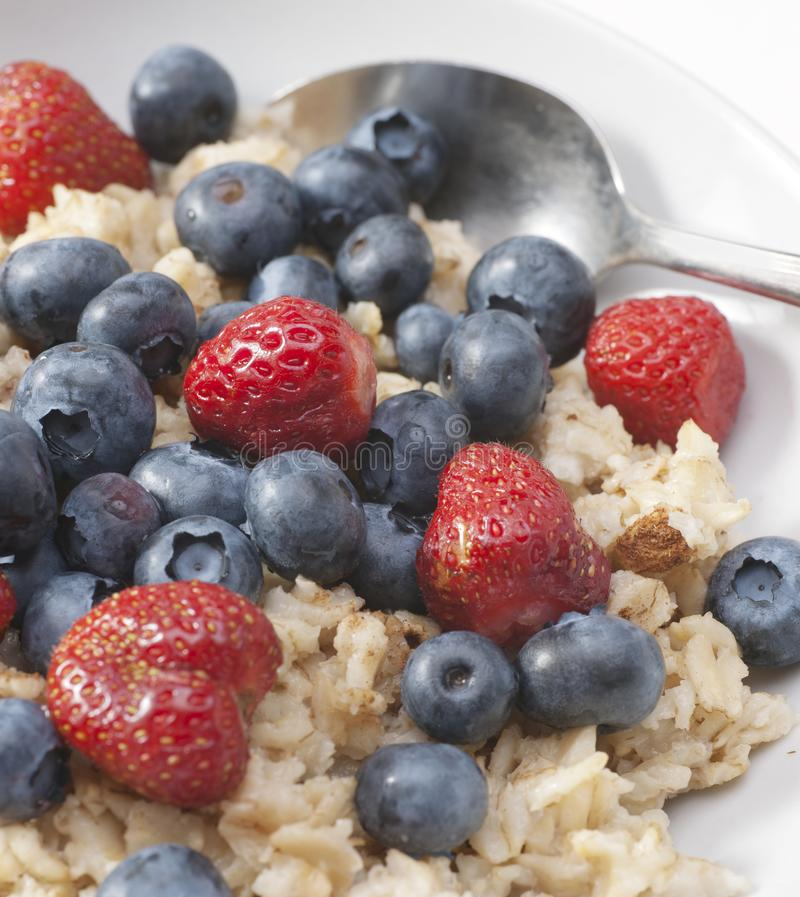 Oatmeal Breakfast  with Berries. Healthy vegetarian breakfast of oatmeal, strawberries, and blueberries in white dish with metal spoon royalty free stock photos